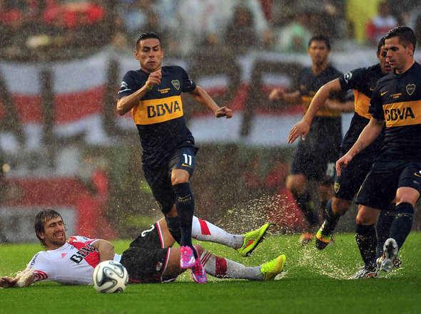 """CARRIZO. EL """"11"""" de Boca puso una pelota fantástica en el gol de Magallán. Aquí, lo acompaña Gago, lo sufre Ponzio, en el suelo."""