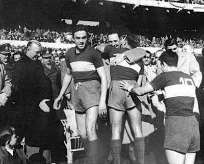 BOCA Y PERÓN. Roberto Rolando --posterior héroe de este clásico-- abraza con afecto al General. Juan Vairo espera su turno. Fue antes del superclásico de la 12° fecha de 1953.