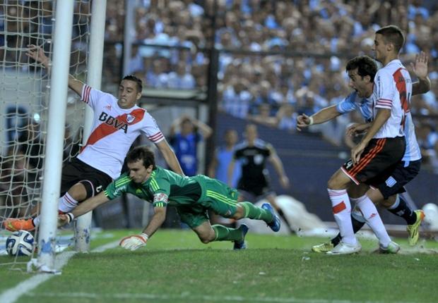 CARAMBOLA. La pelota ya hizo su recorrido de flipper. Dio en Funes Mori y se mete despacito. Barovero gatea sin éxito, Diego Milito grita como un desaforado. Racing logra el gol que lo lleva a la punta del torneo.