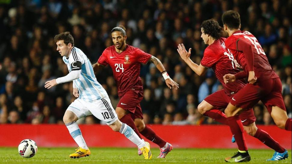 INALCANZABLE. Tres portugueses persiguen a Leo en el amistoso del 18 de noviembre de 2014. Fue su segunda presencia con el Tata Martino como DT.